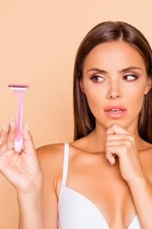 Gesichtshaare entfernen, Frau mit Rasierer in der Hand
