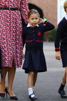 Ein aufregender Tag für Prinzessin Charlotte: Am Tag ihrer Einschulung wirkt die 4-Jährige noch etwas verunsichert in ihrer blauen Schuluniform; spielt immer wieder verlegen an ihrem Haarzopf herum. Doch an ihrer Schultasche baumelt auch ein kleines Accessoire, eine Art Glücksbringer – ob sie ihn wohl zum großen Tag von Mama und Papa geschenkt bekommen hat?