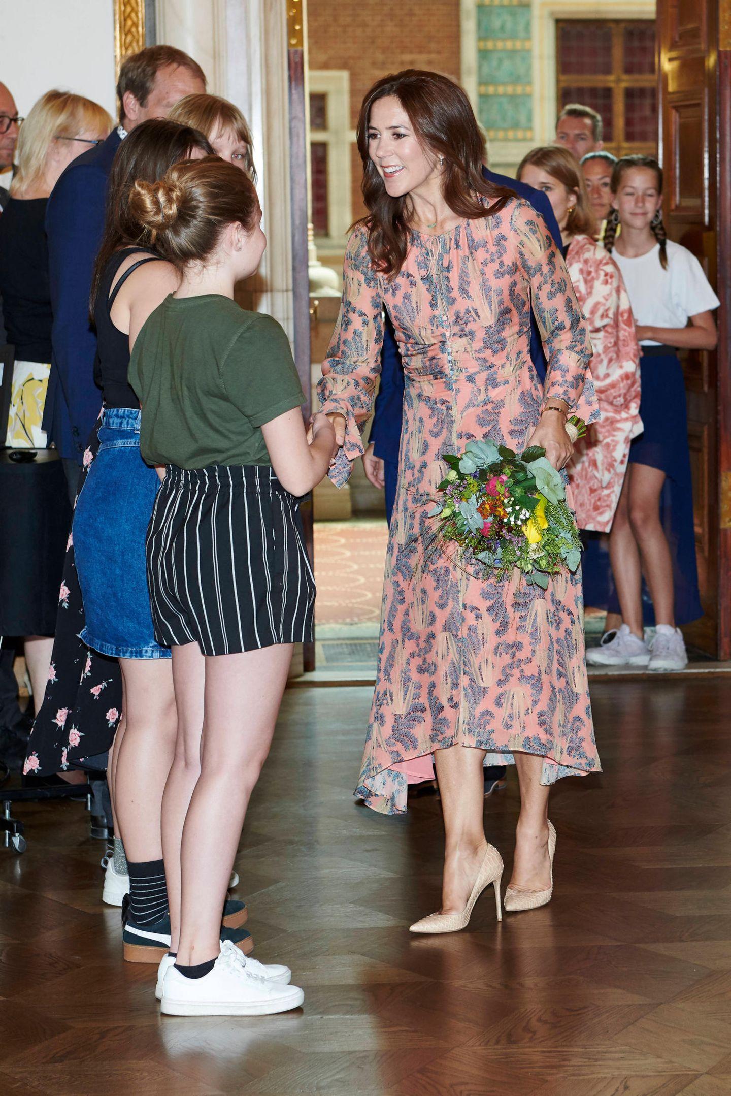 In einem korallfarbenenSeidenkleid aus der Conscious-Kollektion von H&M besucht Prinzessin Mary ein Event in Kopenhagen. Das gemusterte Midi-Dress für rund 179 Euro wird aus Bio-Seide gefertigt und hat eine elegante Raffung mit Drapageeffekt in der Taille. Dazu kombiniert Mary beigefarbene Pumps von Gianvito Rossi und trägt ihre schönen Haare offen. Ein Look, der der Prinzessin so sehr gefällt, dass sie ihn nicht zum ersten Mal trägt ...