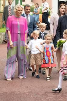 Sie trägt ein luftiges Ensemble in Pink, Lila und Grün. Was auf den ersten Blick aussah wie ein Kleid, entpuppt sich als sommerlicher Jumpsuit. Dazu kombiniert sie Sandalen.