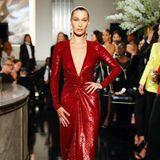 Vor der glamourösen Kulisse der Show von Ralph Lauren präsentiert Bella Hadid eins der Designs: eine rote Glitzerrobe mit tiefem V-Ausschnitt.