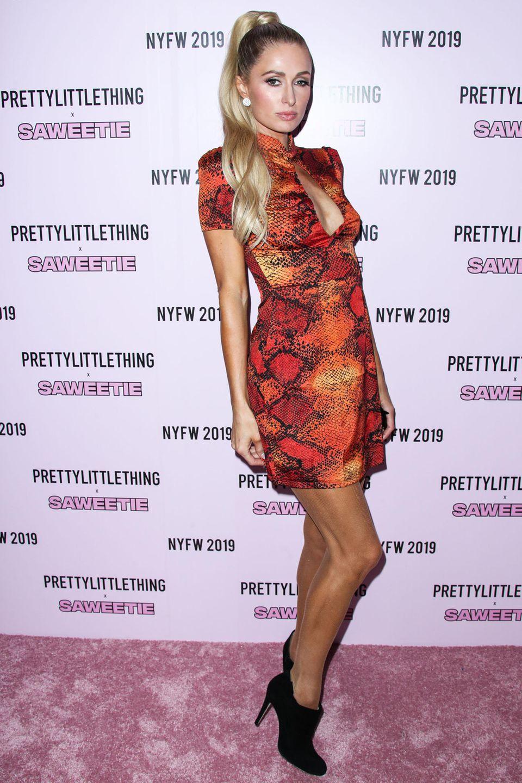 Paris Hilton posiert in einem roten Mini-Lederkleid mit Snake-Print auf dem roten Teppich des Labels Pretty Little Thing.