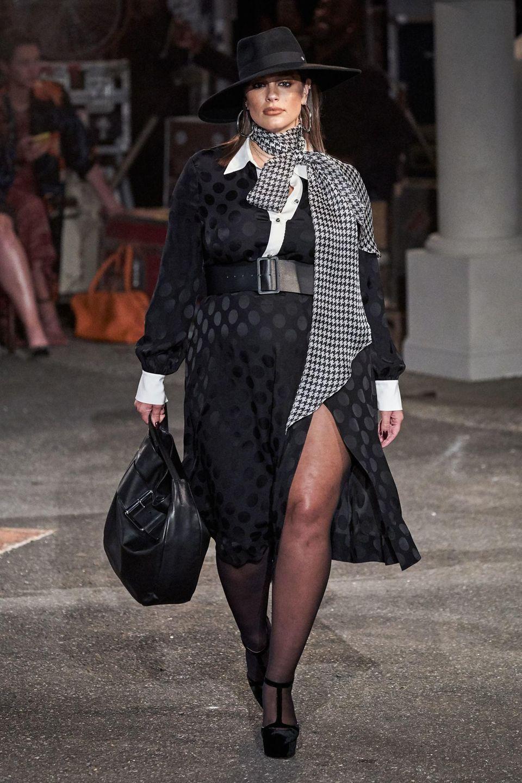 Curvy-Model Ashley Graham läuft in einem schwarzen Maxi-Kleid mit tiefem Beinschlitz und breitem Taillengürtel für den Mode-Guru Tommy Hilfiger über den Laufsteg.