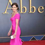 Auch Elizabeth McGovern strahlt in einer pinkfarbenen Robe mit Schleppe bei der Filmpremiere in London. Ein besonders schöner Kontrast: Die Schauspielerin wählt zum knalligen Kleid rote Pumps.