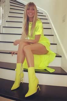 Was für ein Knaller-Look: In einer einem neongelben Vokuhila-Kleid und farblich passenden Stiefeletten mit Pfennigabsätzen strahlt Topmodel Heidi Klum in die Kamera. Bei ihrem Outfit wird selbst die heimische Treppe zum Red-Carpet.
