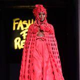 Auch auf dem Catwalk präsentiert Naomi eine extravagante Robe mit Cape und Kopfbedeckung in der Knallfarbe rot – und erneutem Wow-Dekolleté.