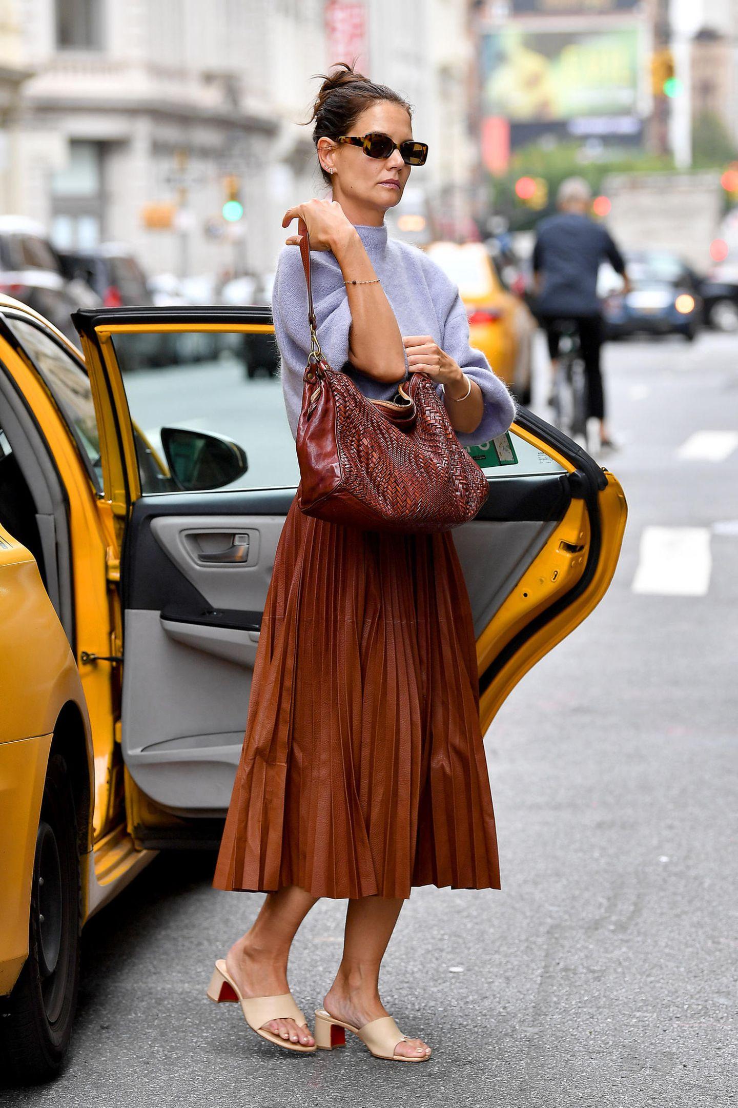Mindestens genauso wichtig, wie ein Taxi in New York stylisch zu rufen, ist es, auch aus einem auszusteigen. Und das beherrscht Katie Holmes par excellence. In einem braunen Plisseerock und einem fliederfarbenen Wollpullover stellt die Schauspielerin ihr Gespür für Mode unter Beweis.