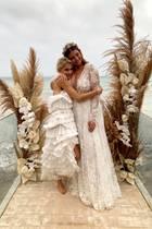 """Star-Bloggerin Farina Opoku, alias Novalanalove, hat auf Ibizia ihrem Freund DJ Yeezy das """"Ja""""-Wort gegeben. Mit dabei ist auch Blogger-Freundin Caro Daur, die zu diesem besonderen Anlass ein weißes Volant-Kleid in Midi-Länge wählt. Passend zur Strandhochzeit verzichtet die hübsche Blondine auf Schuhe."""