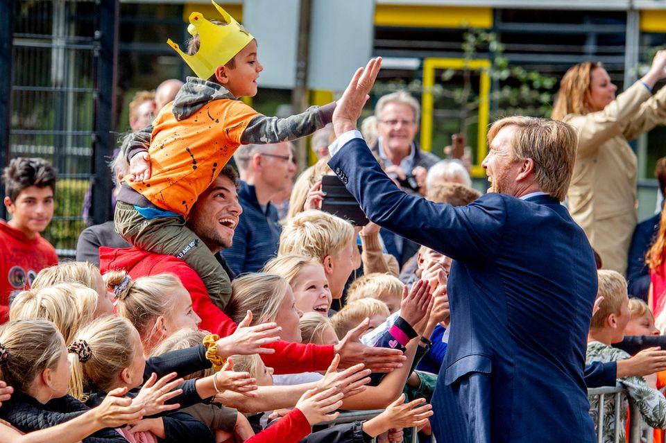 Weiter geht es mit einem Besuch in Veeningen. Dort gibt es von Willem-Alexander ein High-five für einen Mini-König.