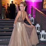 Isabel Edvardsson dreht in ihrem auffälligen Kleid von Crusz eine Pirouette auf den Stufen. Dunkelroter Lippenstift und eine elegante Hochsteckfrisur machen ihren Look noch glamouröser!