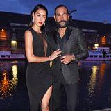 """Was für ein Traumpaar! Rebecca Mir und Massimo Sinato zeigen sich beide komplett in Schwarz. Die durchsichtigen Einsätze und der hohe Beinschlitz ihres Akris-Kleides setzen die tolle Figur des Models perfekt in Szene - das findet auch Ehemann Massimo und schreibt auf Instagram """"Ich Glücklicher"""" zu einem Video von Rebecca."""