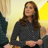 Ihr Haar trägt Herzogin Catherine zu sanften Wellen gestylt - goldfarbene, hängende Ohrringe runden ihren Look ab.