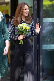 Überraschungs-Auftritt von Herzogin Catherine. Kate besucht das Sunshine House Children and Young Peopleâs Health and Development Centre in London und punktet nicht nur mit ihrer einfühlsamen Art, sondern auch mit ihrem Outfit. Zu einer schwarzen, weit geschnittenen Hose kombiniert Kate eine schwarz-weiß gepunktete Bluse und schlichte, schwarze Pumps.
