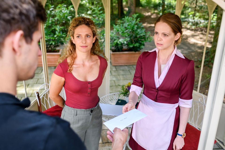 """""""Sturm der Liebe"""": Lucy (Jennifer Siemann, r.) übergibt Paul (Sandro Kirtzel, l.) mit schlechtem Gewissen eine Kopie von Romys Brief, die sie mit Franzi (Léa Wegmann) angefertigt hat."""