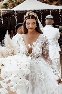 Ihre Haare trägt die Bloggerin leicht gewellt und teilweise zurückgesteckt. gekrönt wird Farina Opokus Hochzeits-Look mit einer filigranen, goldenen Krone.