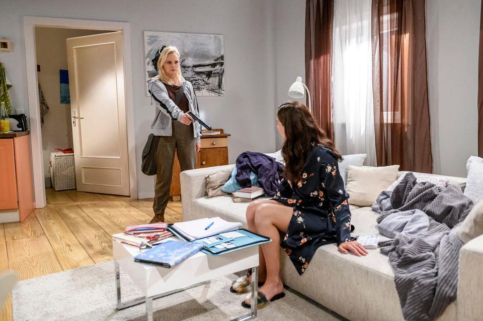 Annabelle (Jenny Löffler, l.) fordert die geschockte Denise (Helen Barke, r.) mit gezückter Waffe auf, einen Abschiedsbrief zu schreiben.