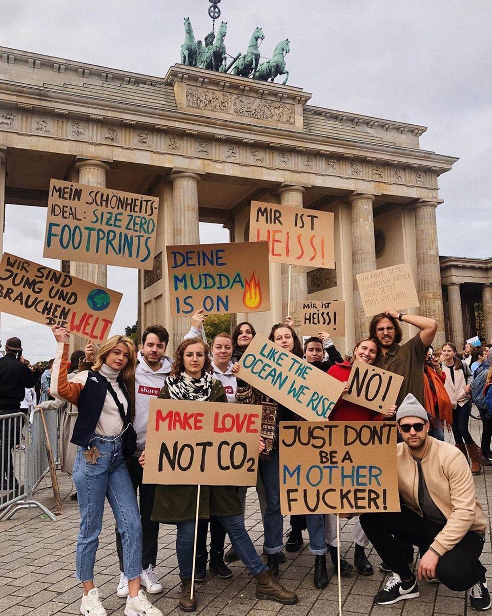 Vor dem Brandenburger Tor in Berlin schließen sich Schauspielerin Lias-Marie Koroll und ihre Freundemit kreativen Plakaten dem weltweiten Klimastreik an.