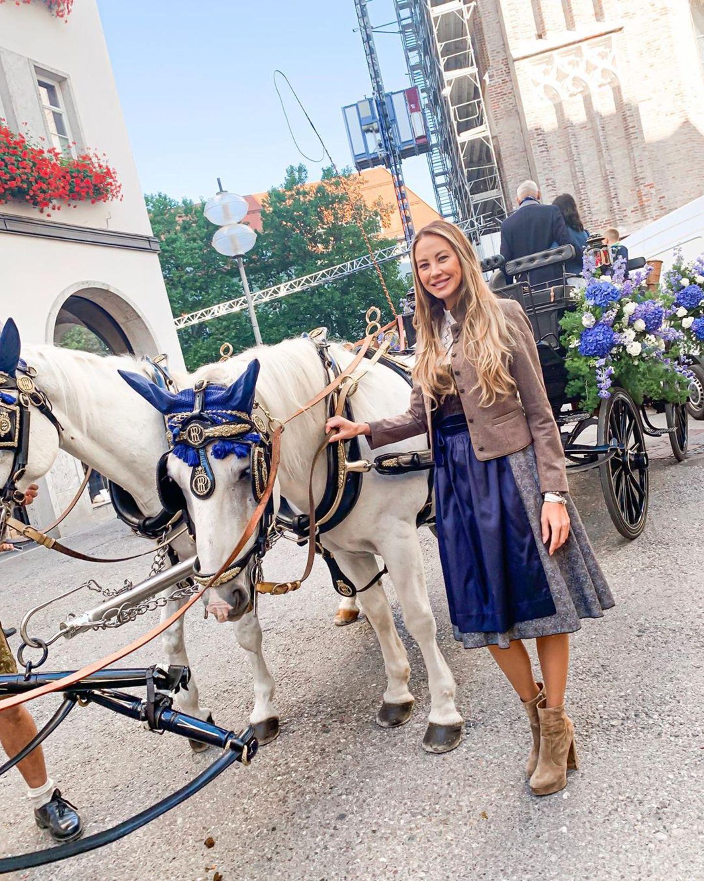 Das Dirndl vonAlessandra Meyer-Wölden passt farblich gut zu dem Kopfschmuck der Pferde und den Blumen an der Kutsche.