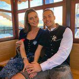 Mit einem Selfie aus der Riesenradgondel grüßen Jennifer Lange und Andrej Mangold. Beide entscheiden sich für blaues Samt an ihren jeweiligen Trachten aus dem Hause Angermaier und machen damit dem strahlend blauen Himmel über München Konkurrenz.