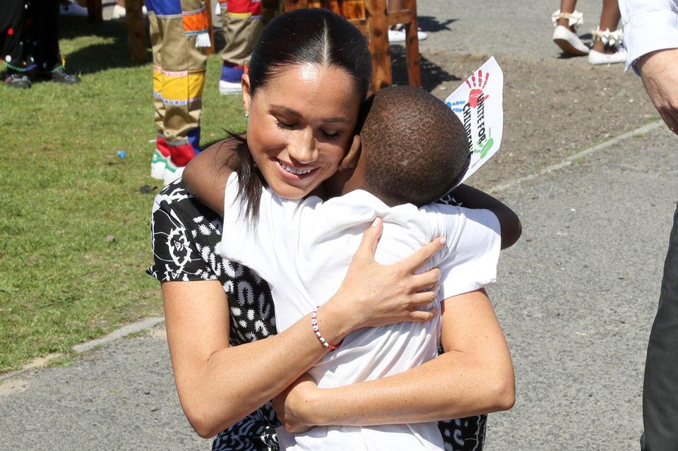 Rührender Moment: Meghan wird von einem kleinen Fan innig umarmt.