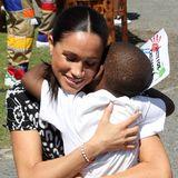 Prinz Harry + Herzogin Meghan: Beim Besuch im Township Nyanga scheint der royale Besuch bei den Bewohnern gut anzukommen. Einer der kleinen Fans schenkt Herzogin Meghan eine besonders innige Umarmung, die diese offensichtlich gerne annimmt.