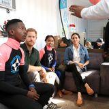 """Prinz Harry + Herzogin Meghan: Interessiert hören sich Harry und Meghan an, was """"Waves for Change"""" in der Region leistet. Die Organisation unterstützt lokale Surf-Mentoren, die Therapie-Angebote für Jugendliche aus sozial benachteiligten und gewalttätigen Gemeinschaften anbieten."""