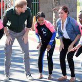 """Prinz Harry + Herzogin Meghan: Am zweiten Tag ihrer Afrika-Reise sind Prinz Harry und Herzogin Meghan bei der NGO """"Waves for Change"""" in Monwabisi Beach zu Gast. Von der jungen Surferin bekommt das Paar gleich ein paar Tricks fürs Board gezeigt."""