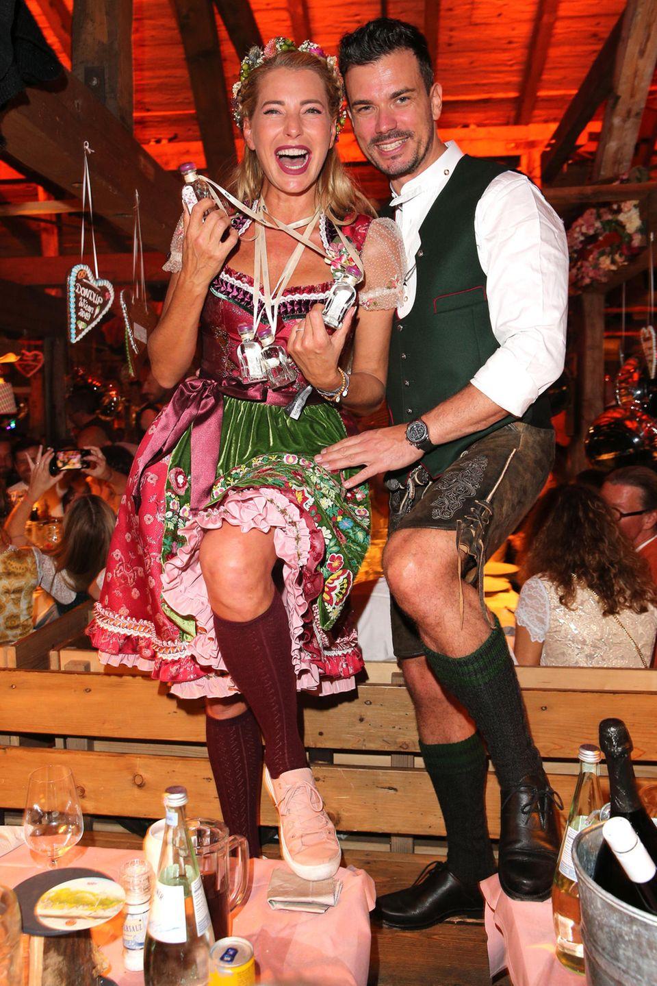 Giulia Siegel und ihr Partner Ludwig Heer tanzen ausgelassen auf den Bierzeltbänken.