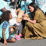 Prinz Harry + Herzogin Meghan: Meghan bekommt ein Sträußchen bunter Blumen überreicht. Gerührt von der Geste bedankt sich die Herzogin bei dem netten Mädchen.
