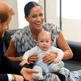 Prinz Harry + Herzogin Meghan: Ganz entspannt sitzt der kleine aufgeweckte Gast auf dem Schoß von Meghan und genießt die Aufmerksamkeit.
