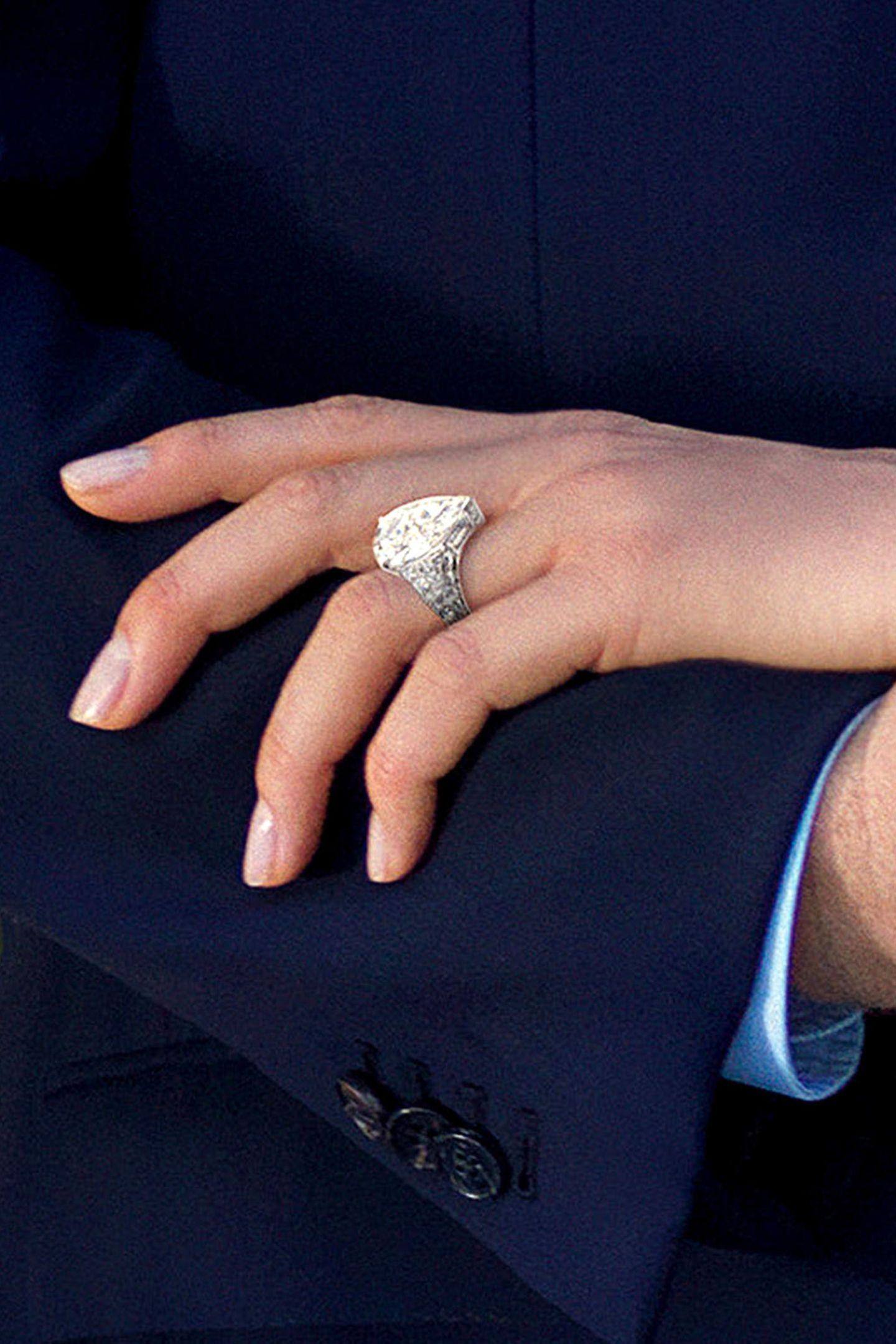 Der Diamantringim Tropfenschliff wird von einermit weiteren wertvollen Steinen besetzten Schiene eingefasst und funkelt pompös vom Ringfinger.
