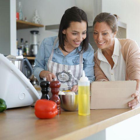 Thermomix-Alternative, Freundinnen lachen in der Küche, gucken auf Tablet-PC, kochen, Küchenmaschine