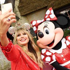 """28. September 2019  Heidi Klum posiert im Partnerlook mit ihrem Fashion-Vorbild Minnie Mouse im kalifornischen Disneyland. Anlass für das Treffen der beiden stylischen Mäuseist die Präsentation der von Heidi designten und mitSwarovski-Kristallen bestücktenMinnie-Maus-Ohren für die""""Disney Parks Designer Collection""""."""