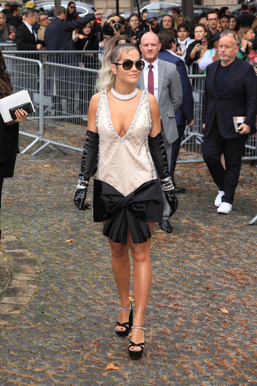 Mit XXL-Schleife am Kleid und schwarzen, eleganten Handschuhen besucht Sängerin Rita Ora die Show des Modelabes Miu Miu in Paris.