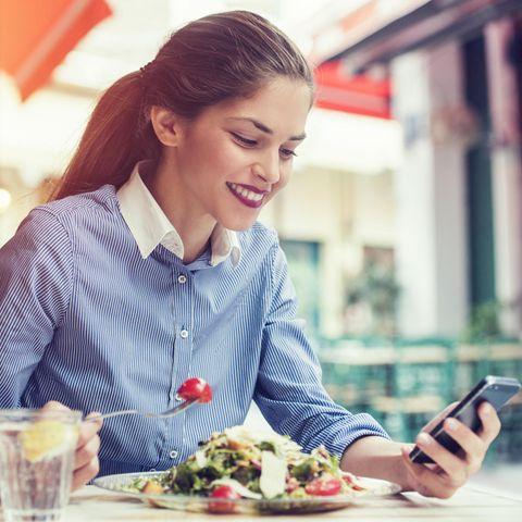 Frau beim Essen und Sms schreiben