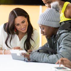 """Prinz Harry + Herzogin Meghan: Herzogin Meghan unterhält sich mit einem Teilnehmer des """"YES""""-Programms, das in den nächsten drei Jahren eine Millionen Arbeitsbeschaffungsmaßnahmen für junge Südafrikaner unterstützen möchte."""