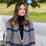 Der graue, klassisch geschnittene Wollmantel wirkt durch das großzügige Karo-Muster in orange und dunkelblau modern und gar nicht spießig – ein perfektes Teil für den Herbst.