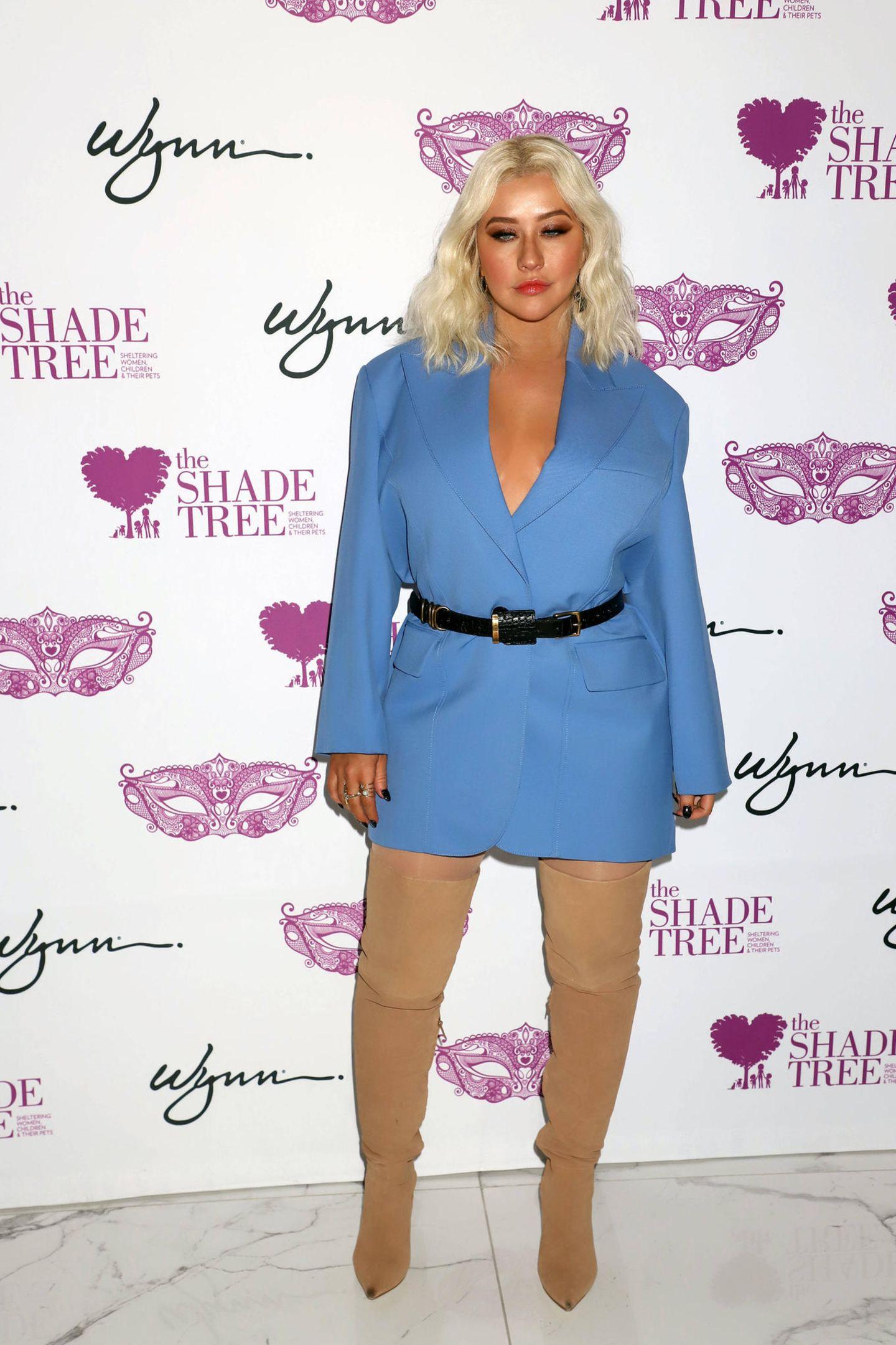 """Im Oktober 2019 weiß Christina Aguilera ihre Kurven richtig zu betonen: Im hellblauem Blazerkleid mit Taillengürtel und beigefarbenen Overknee-Stiefel erscheint siebei der The Shade Tree's """"Mask Off Gala"""" in Las Vegas."""