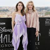 """Angelina Jolie und Michelle Pfeiffer strahlen beim Photocall von """"Maleficent 2"""" in Romum die Wette: Angelina trägt ein drapiertes Longtop in flieder von Givenchy, dazu eine schwarze Hose und schwarze Pumps. Michelle setzt in ihrer roséfarbenen Seidenbluse ebenfalls auf Pastell."""