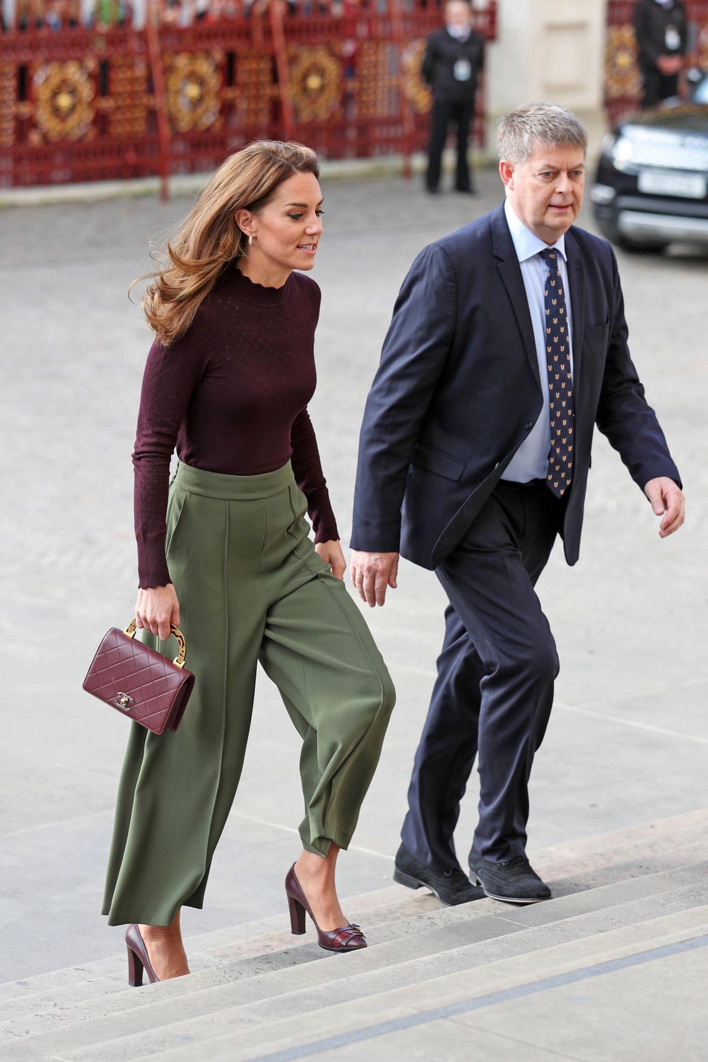 Catherine trägt einen hautengen, raffinierten Rollkragen-Pullover in einem Bourdeaux-Ton (von Warehouse, ca. 46 Euro). Dazu wählt die Herzogin eine weite Hose in Grüntönen, Pumps - ebenfalls in bordeauxrot und eine luxuriöse Handtasche von Chanel.