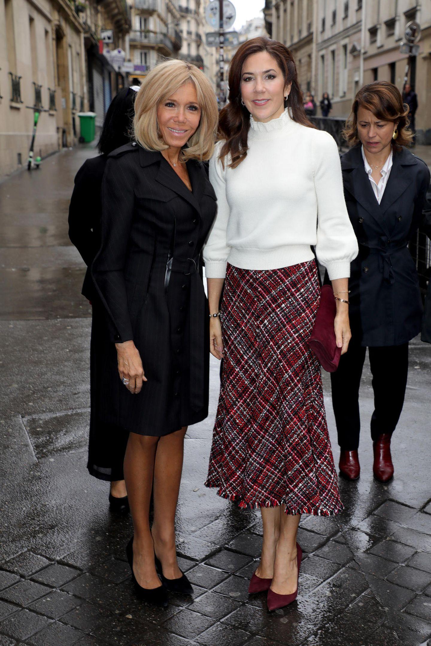 Von Kopf bis Fuß perfekt gestylt – so präsentiert sich Brigitte Macron beim Besuch einer Schule in Paris. In einem schwarzen, knielangen Ensemble, das dank der schönen Knopfleiste und des Taillengürtels zu einem aufregenden Hingucker wird, lässt sie sich bei dem Termin an der Seite von Prinzessin Maryfotografieren. Doch das wahre Style-Highlight trägt die französische First Lady an ihren Füßen ...