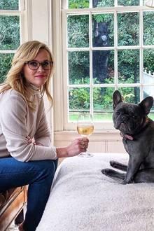 In netter Gesellschaft trinkt es sich viel besser:Reese Witherspoon lässt den Tag gemütlich mitihrer französischen Bulldoge Pepper ausklingen.