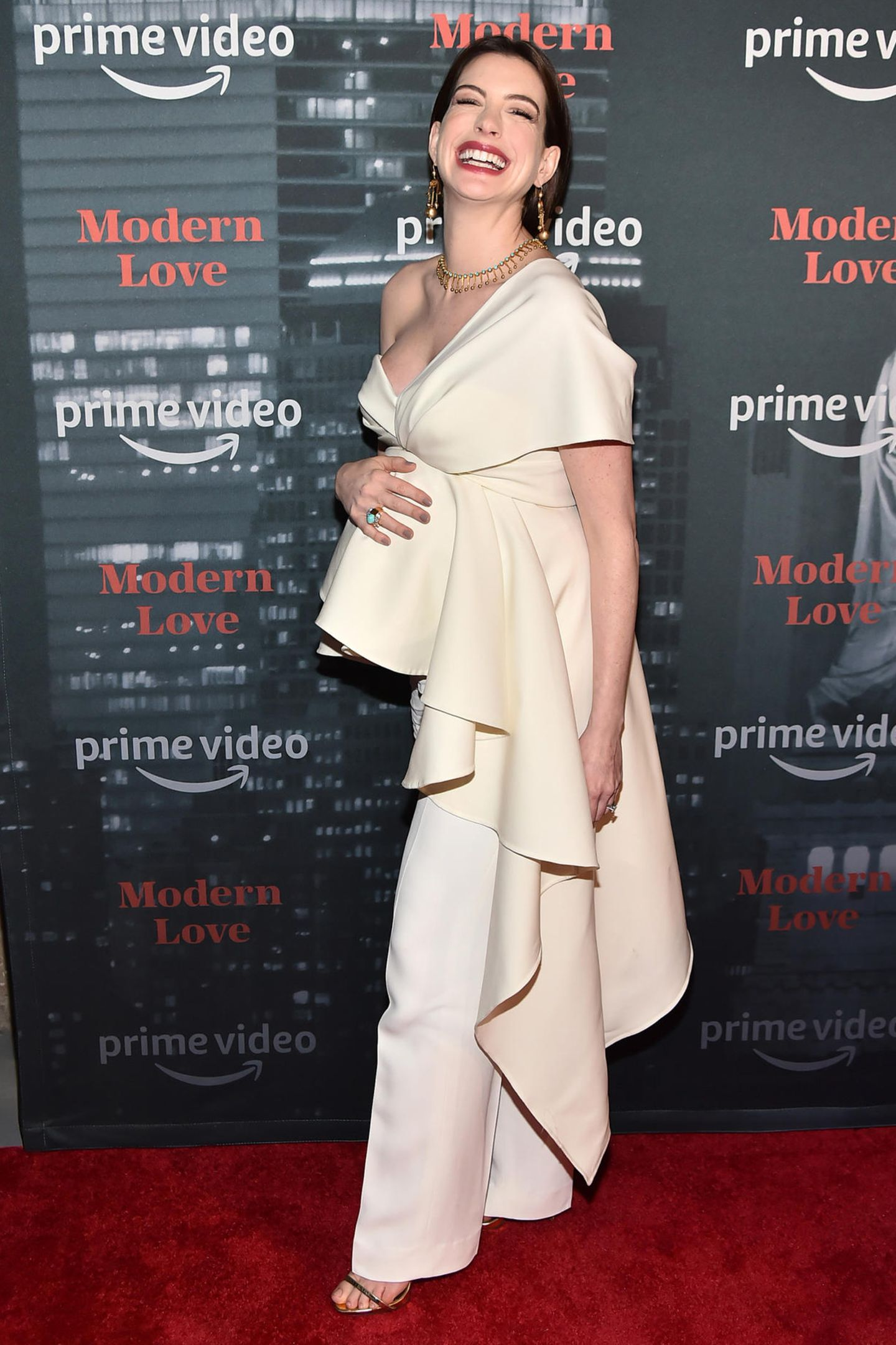 """Hey Mama! Zur Premiere ihrer neuen Serie """"Modern Love"""" setzt Anne Hathaway ihren Babybauch perfekt in Szene. Die Schauspielerin betont ihn mit einem cremefarbenen One-Shoulder-Topmit verspielten Volants, die asymmetrisch an ihrer linken Körperseite herunterfallen. Dazu kombiniert Anne eine weiße Stoffhose und goldene High Heels – gepaart mit ihrem schönsten Lächeln!"""