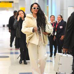 Im kuschligen Reise-Look erwischen Paparazzi Rihanna am Flughafen von New York. Von Kopf bis Fuß zeigt sie sich farblich einheitlich und wählt ein cremefarbenes Outfit. Zu weißen Sneakern trägt die Sängerin eine weiße, flauschige Trainingshose samt dazu passender Trainingsjacke sowie eine Weste aus Kunstfell. Ein Reise-Ensemble, das zwar kuschlig, aber in einem Punkt dennoch unpraktisch ist ...