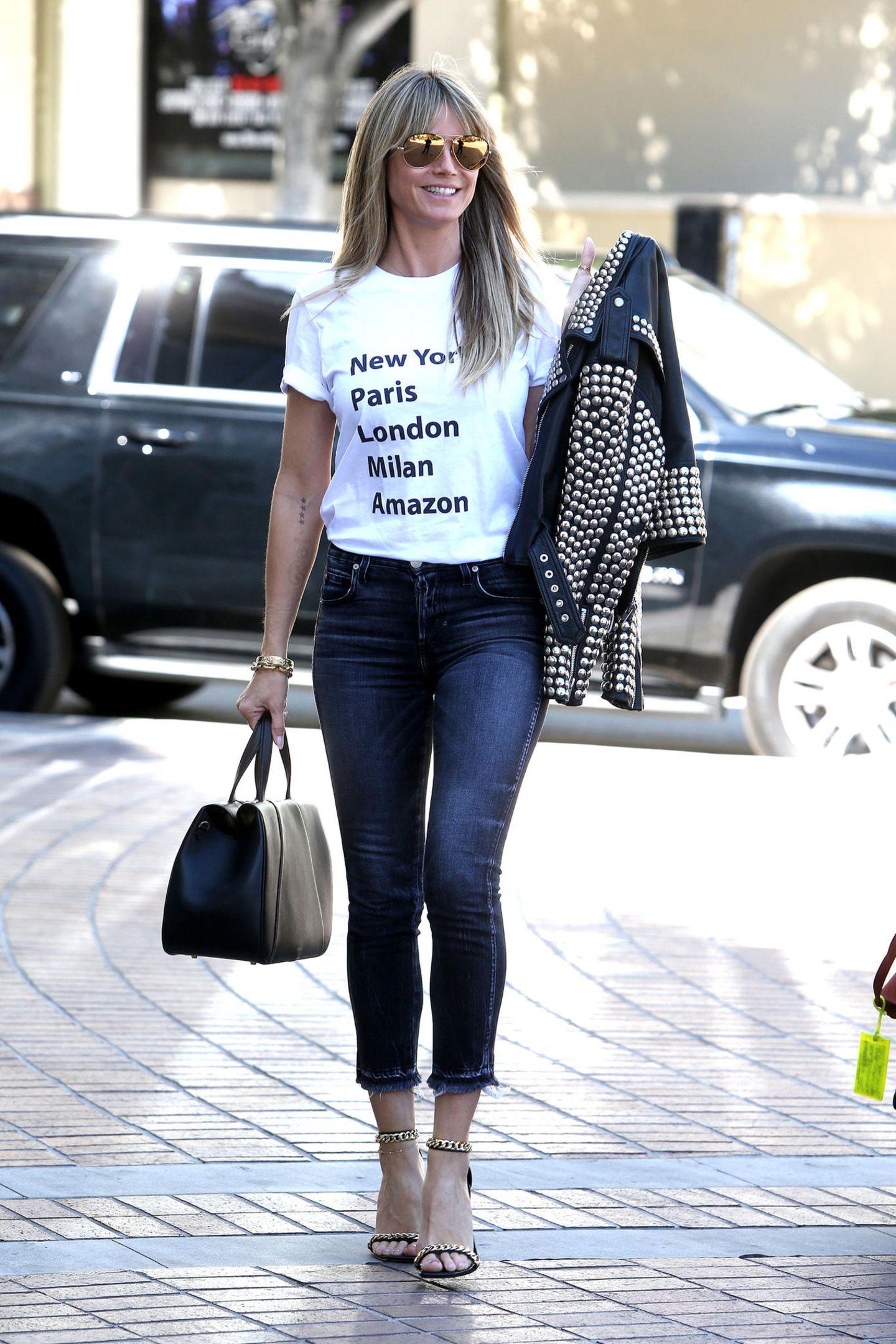 Heidi Klums Biker-Look ist gar nicht derb, sondern supersexy! Womit manin der rustikalen Biker-Welt womöglich anecken würde, ist in der schillernden Welt von Los Angeles völlig in Ordnung. Zueiner blauen Skinny-Jeans trägt sie ein mit schwarzen Lettern bedrucktes weißes T-Shirt – der Hingucker ist jedoch ihre lederne und mit Nieten bestückte Bikerjacke, die das Model lässig über linke Schulter wirft. Und noch etwas sorgt für diesenWow-Auftritt ...