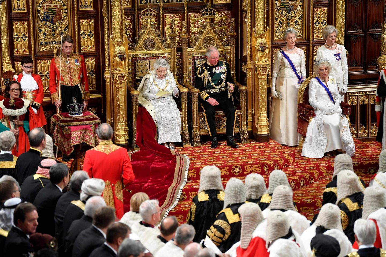 Um nicht gänzlich mit der Tradition zu brechenwurde die Krone in diesem Jahr neben der Königin auf einem Tisch platziert. Begleitet wurde die Queen übrigens von ihrem Sohn Prinz Charles und ihrer Schwiegertochter Camilla.