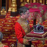 """Nur selten hat die Queen bisher auf die Imperial State Crown, die traditionsgemäß während der Parlamentseröffnung vom Monarchen getragen wird, verzichtet. 1952, beim ersten Mal, war sie noch nicht gekrönt und durfte die Krone deshalb nicht tragen.2017 und 1974 ersetzte sie die Krone durch einen Hut und ihre Staatsrobe durch ein einfaches Kostüm. Grund: Aufgrund vorgezogener Parlamentswahlen entschied man sich laut britischen Medien für ein""""simplere Version"""" der Eröffnung. 2019, so munkelt die britische Presse, sei der inzwischen 93-jährigen Queen die 2,5 Pfund (etwa 1,1 Kilogramm) schwere Krone schlichtweg zu schwer gewesen."""