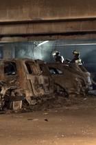 Feuerwehrmänner begutachten die ausgebrannten Autos im Parkhaus des Flughafens Münster Osnabrück.