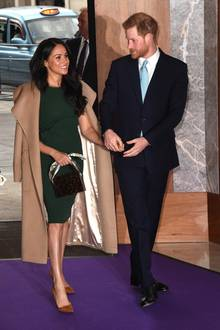 """Bei ihrem Auftritt bei den """"WellChild Awards"""" setzen Herzogin Meghan und Prinz Harry auf gedeckte Farben und verstehen es dabei, zu strahlen. Während der in einen dunkelblauen Anzug gekleidete Herzog von Sussex mit einer hellblau-gemusterten Krawatte Akzente setzt, rückt seine Frau als Accessoire eine mit Plattschild besetzte Abendtasche in den Fokus. Witziges Detail: der """"Henkel"""" des nützlichen Schmuckstücks ist ein mit Créme- und Blautönen verziertes Seidentuch."""