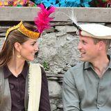 16. Oktober | Tag 3  Schatz, wie siehst du denn aus? Kate (mit Feder-Stirnband) und William (mit Regimentsmütze der Chitral Scouts) bestaunen ihre Kopfbedeckungen. Bei dem ungewöhnlichen Anblick können sich die beiden Royals das Lachen nicht verkneifen.
